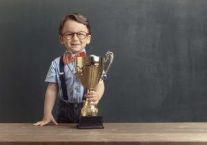 Маленький мальчик в очках держит кубок